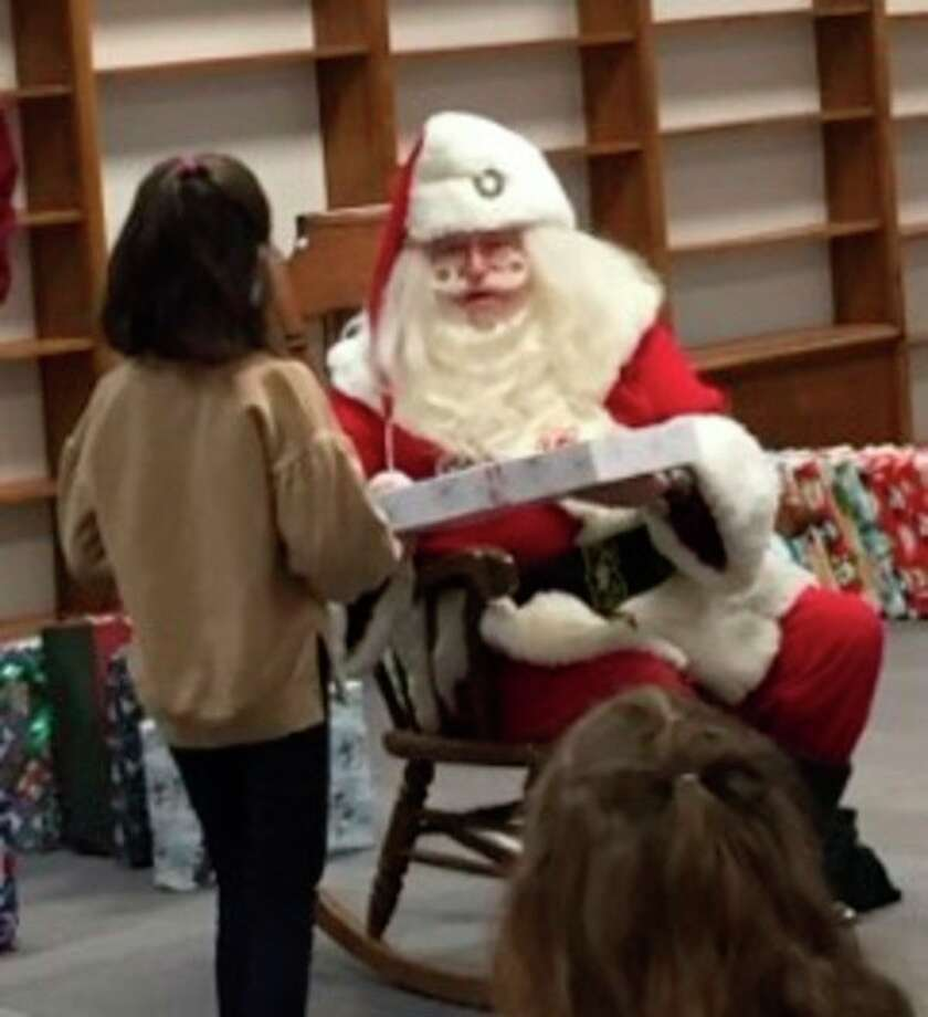 A student at Central Park Elementary School receives a gift during Santa's recent visit, sponsored by local Kiwanis clubs. (Photo provided)