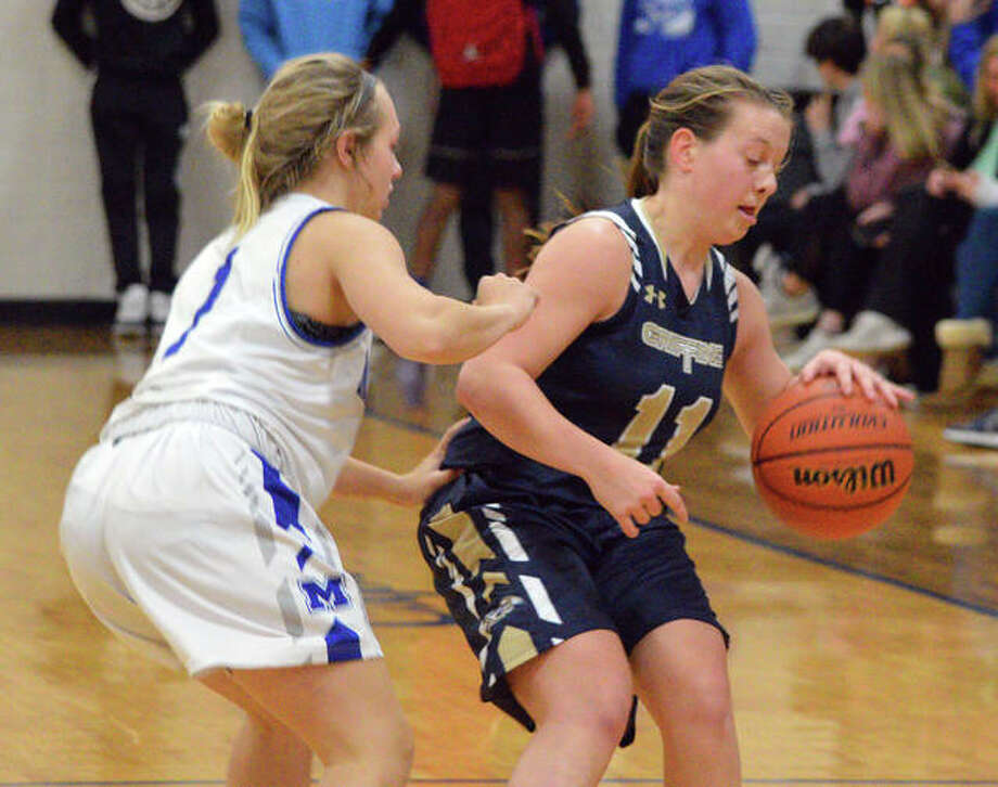 Father McGivney's Macy Hoppes, right, shields the ball away from a Marquette defender during Thursday's game in Alton.