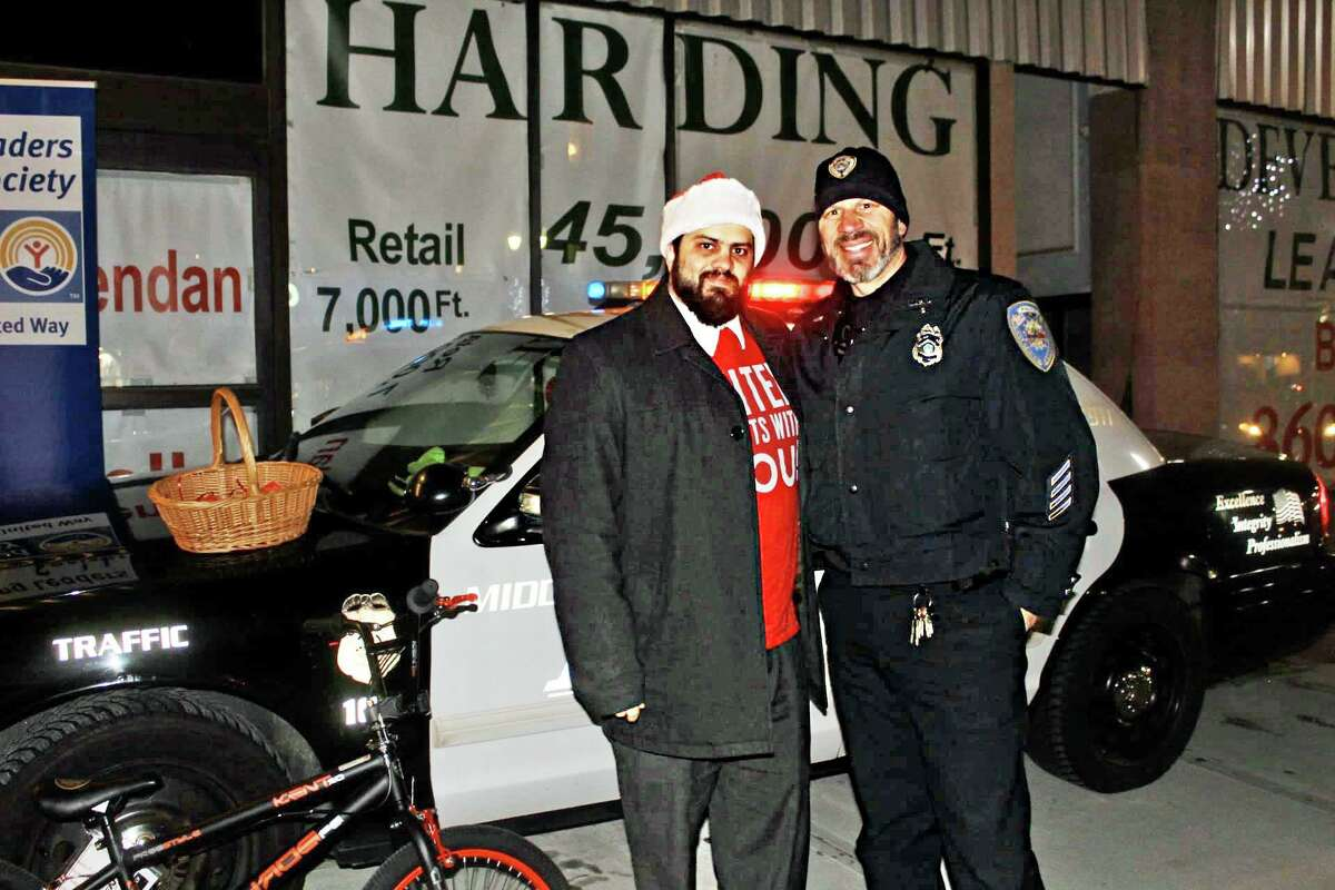 The Middlesex United Way Young Leaders Stuff-a-Cruiser holiday social and toy drive in Middletown gathered hundreds of gifts for local teens. From left are Kevin Harris of Chester, chairman of the Young Leaders Society, and Middletown Police Officer Anthony Knapp.