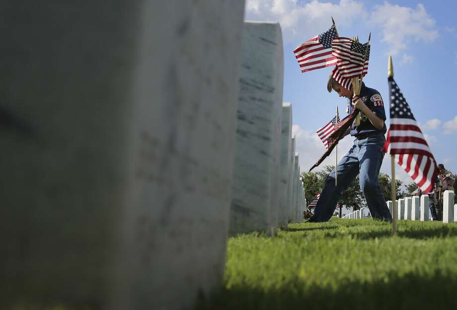 Garrett Theisen, 10, from Pack 651, Lackland Air Force Base holds onto a handful of flags as he plants one in front of a headstone at Fort Sam Houston National Cemetery on Friday, May, 24, 2019. The tribute marked the start of a long Memorial Day weekend in the Alamo City. Several hundred scouts from the Alamo Area Council - the local scouting organization - meticulously placed flags on each of the 110,000 headstones at the national cemetery. Photo: Kin Man Hui/Staff Photographer
