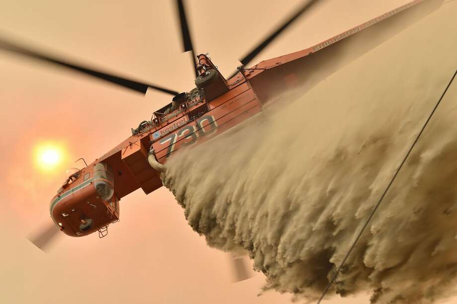 A helicopter drops fire retardant Thursday to protect property in Balmoral, a city about 90 miles southwest of Sydney. Record heat has fanned the wildfires. Photo: Peter Parks / AFP Via Getty Images