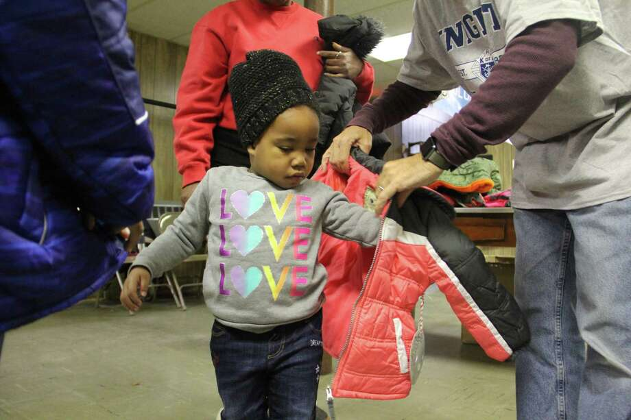 Children receive free coats from the Knights of Columbu Coats for Kids drive on Friday, Nov. 24, at St. John the Baptist Church in New Haven. Organizers said 300 coats were available for children. Photo: Esteban L. Hernandez / Hearst Connecticut Media