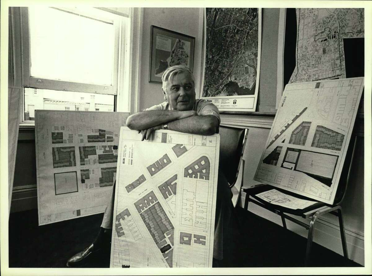 Ed Logue poses in his South Bronx office in the 1980s, surrounded by graphic evidence of development plans for the beleaguered New York City community.