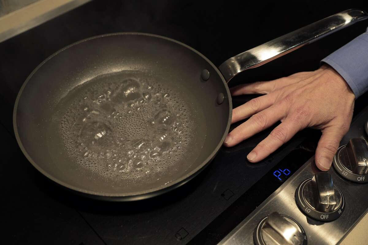 Wei-Tai Kwok places his hand on an induction cooktop in his kitchen, where he replaced natural gas appliances with electric ones.