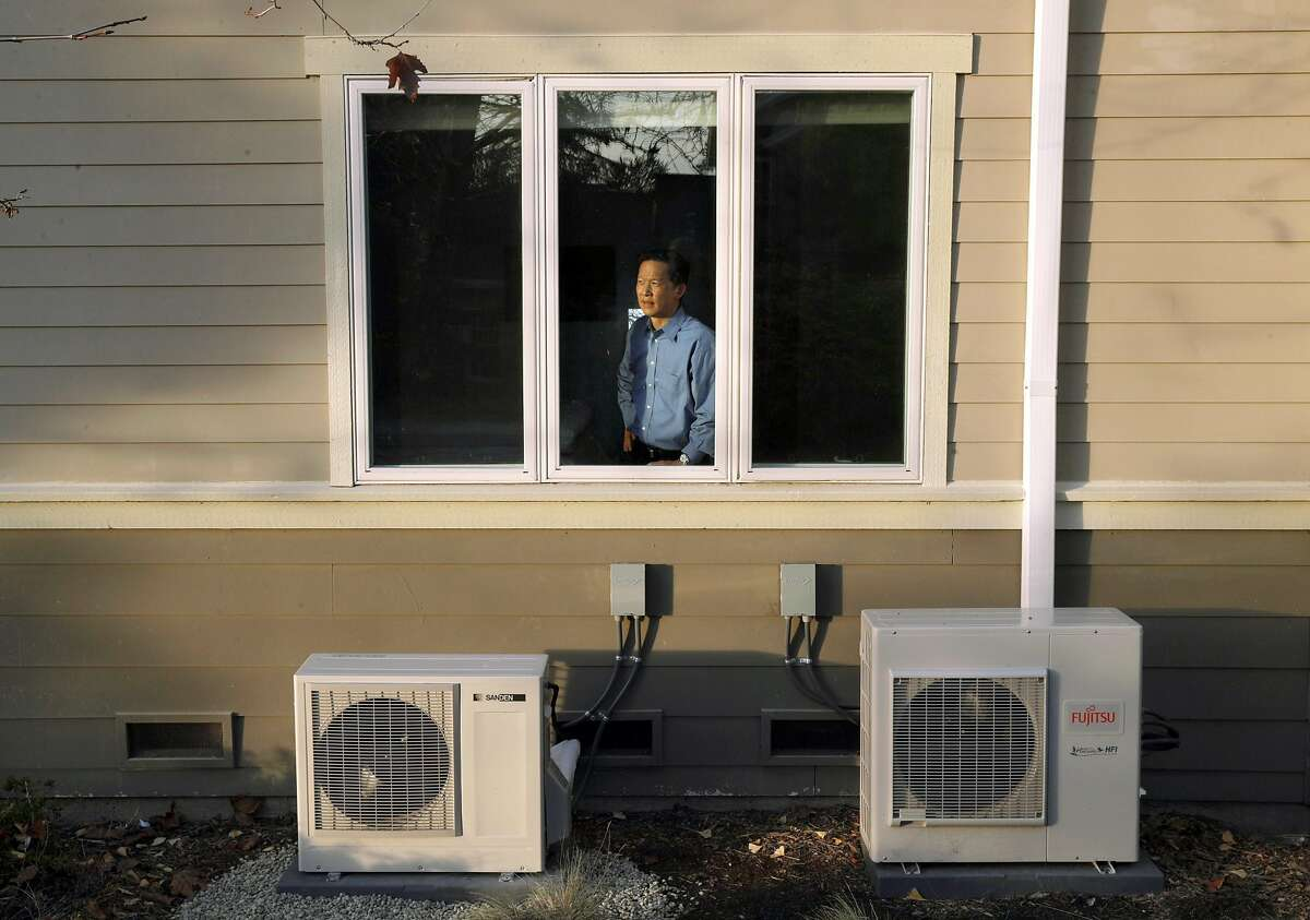 Wei-Tai Kwok with the two compressors for his water heater and ductless heating/cooling units at his home that he completely converted to electric to stop using natural gas in Lafayette, Calif., on Monday, December 16, 2019. In January, new state requirements requiring rooftop solar panels on new homes will go into effect. At the same time, many municipalities are banning gas appliances inside residences and commercial buildings, pushing all-electric construction.