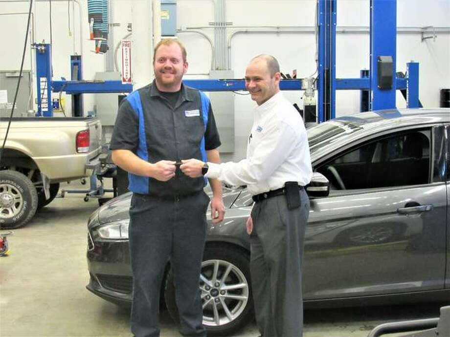 John Roberts of Roberts Motors in Alton, left, hands over the keys to a 2015 Ford Focus to Chris Reynolds of Lewis & Clark Community College. The vehicle will be used in the Automotive Technology Program.