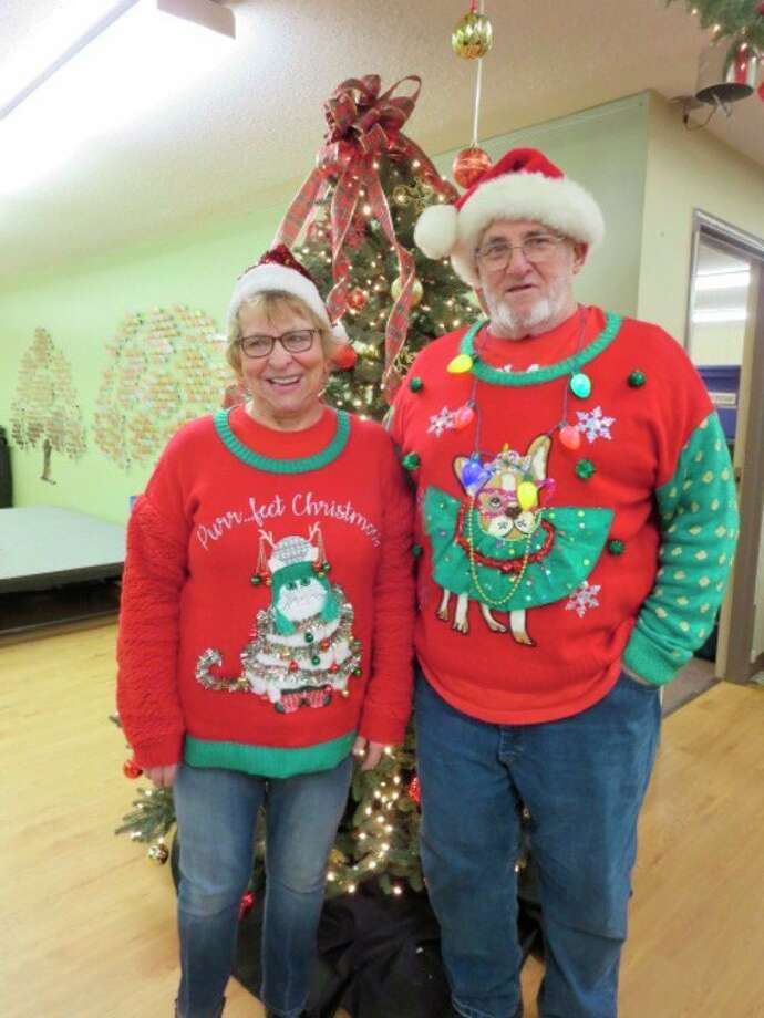 A couple shows off their complimentary sweaters at the senior center. (Courtesy photo)