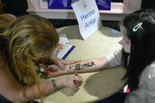 Westporter Christina Dear, left, does some henna work on Tessa Balmer, 9, of Westport, at last year's First Light Festival. The event returns this year at the Westport Museum and other locations in town.