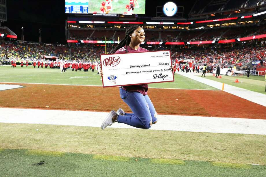 Destiny Alfred of Spring jumps for joy after winning $100,000 through the Dr Pepper Tuition Giveaway. The competition occurred at the PAC 12 Conference Championship game Dec. 6, 2019. Photo: Courtesy Of Dr Pepper