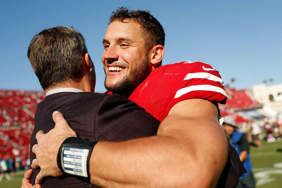 San Francisco 49ers' Nick Bosa hugs General Manager John Lynch after 20-7 win over Los Angeles Rams during NFL game at Los Angeles Coliseum in Los Angeles, Calif., on Sunday, October 13, 2019.