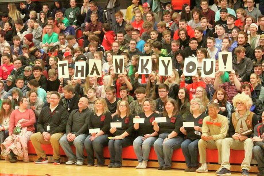 """Students and staff surprised Scharlow by holding up cards that spelled out, """"thank you."""" (Pioneer photo/Catherine Sweeney)"""