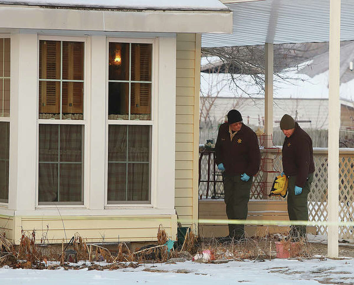 Two Illinois State Police crime scene technicians look around the back door of a house in the 300 block of Mill Street in Bethalto early Friday morning after three bodies were found inside late Thursday night. The Major Case Squad of Greater St. Louis has been activated and is investigating the crime that may be linked to other states.