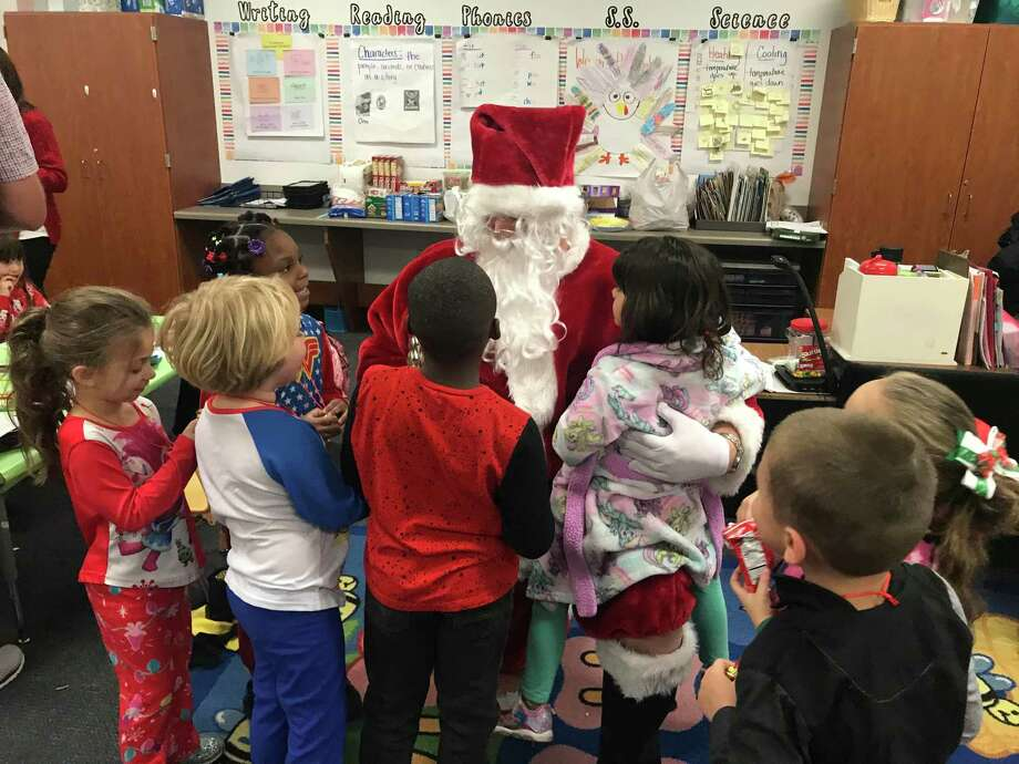 Santa aka. Lion Warner Phelps was bombarded by kindergartens with their wish requests last week as the Conroe Noon Lions Club visited their adopted school of Reaves Elementary. Photo: Courtesy Photo