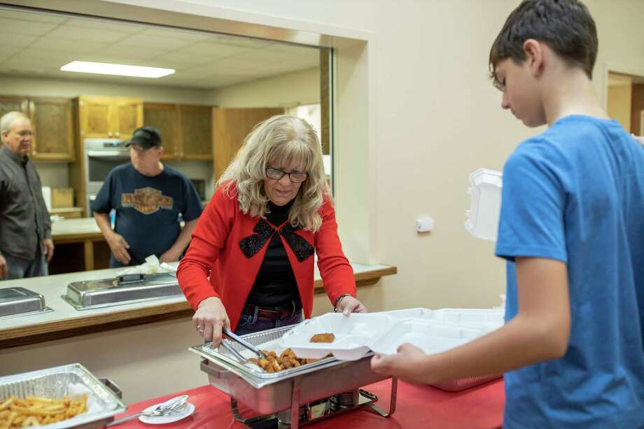 Cheryl Anderson serves fried catfish, hushpuppies, coleslaw and fries during the inaugural Family Promise Christmas Celebration Saturday, Dec. 7, 2019. Attendees paid $10 for a complete catfish dinner in support of the families that are assisted by Family Promise. Photo: Gustavo Huerta, Houston Chronicle / Staff Photographer / Houston Chronicle