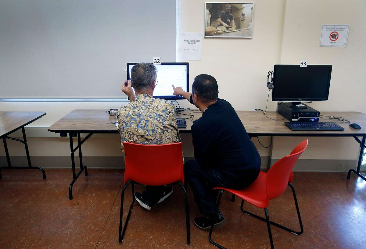 U.S. Census Bureau recruiter Antonio Aguilar-Karayianni (right) assists Raymond Raymond with the application process at a workshop to hire temporary workers for the 2020 census in San Francisco, Calif. on Tuesday, Dec. 10, 2019. The St. Anthony Foundation's Tenderloin Tech Lab is hosting recruiting sessions in collaboration with the Census Bureau.