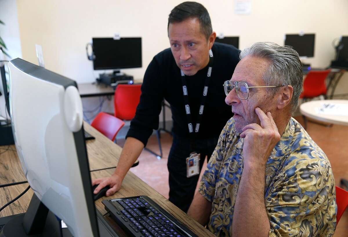 U.S. Census Bureau recruiter Antonio Aguilar-Karayianni (left) assists Raymond Raymond with the application process at a workshop to hire temporary workers for the 2020 census in San Francisco, Calif. on Tuesday, Dec. 10, 2019. The St. Anthony Foundation's Tenderloin Tech Lab is hosting recruiting sessions in collaboration with the Census Bureau.