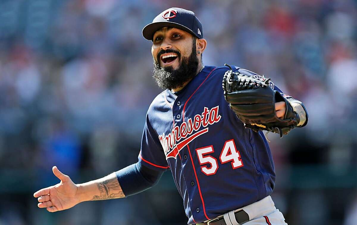 FILE - In this Sept. 14, 2019, file photo, Minnesota Twins relief pitcher Sergio Romo walks back to the dugout with a smile during a baseball game against the Cleveland Indians in Cleveland. The Twins have signed two veteran right-handed relievers, Sergio Romo and Tyler Clippard. Romo joined the team last July in a trade with San Francisco. (AP Photo/Tony Dejak, File)