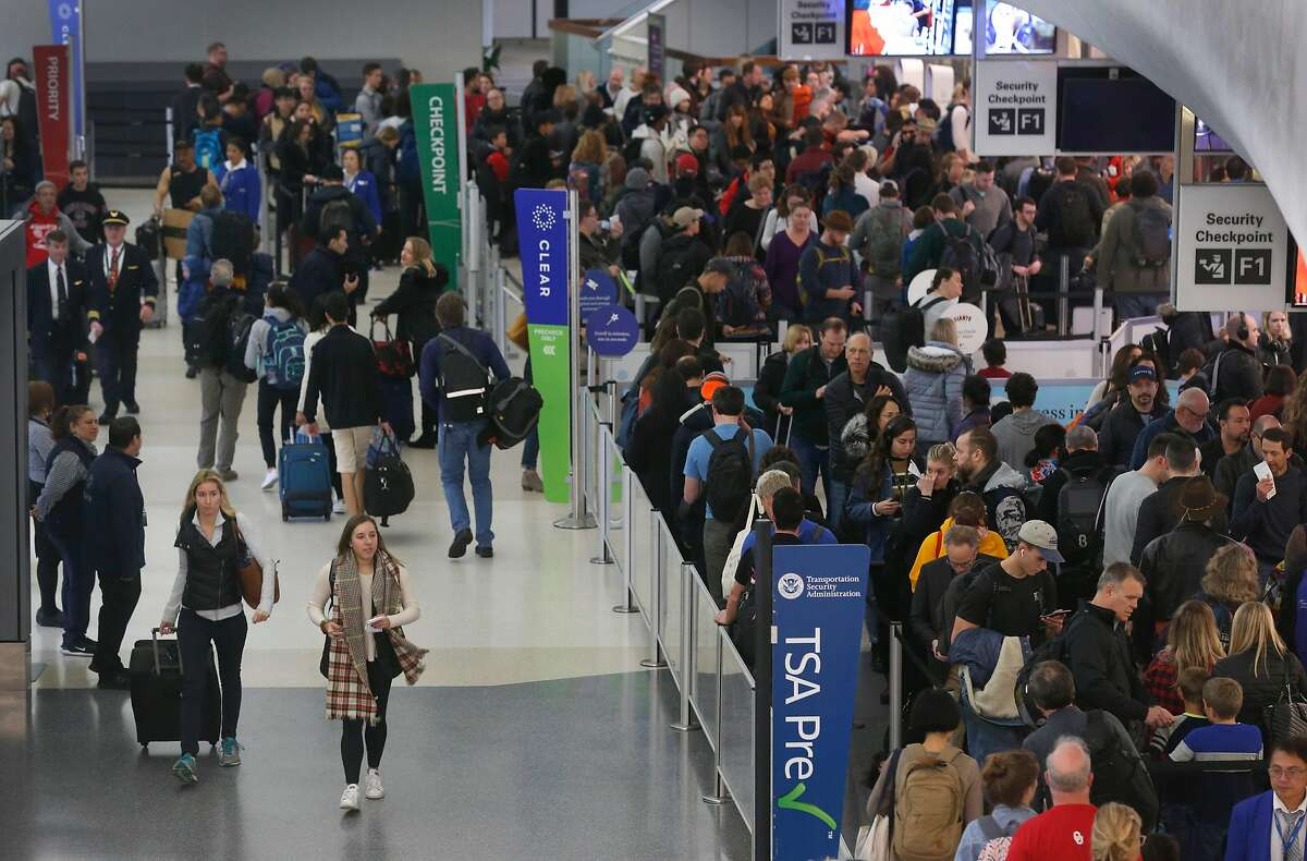 Holiday air travelers wait to pass through security screening in Terminal 3 at SFO in San Francisco, Calif. on Friday, Dec. 20, 2019. Conditions may worsen in the coming days as a rainstorm scheduled to hit the area over the weekend could snarl holiday travel plans.
