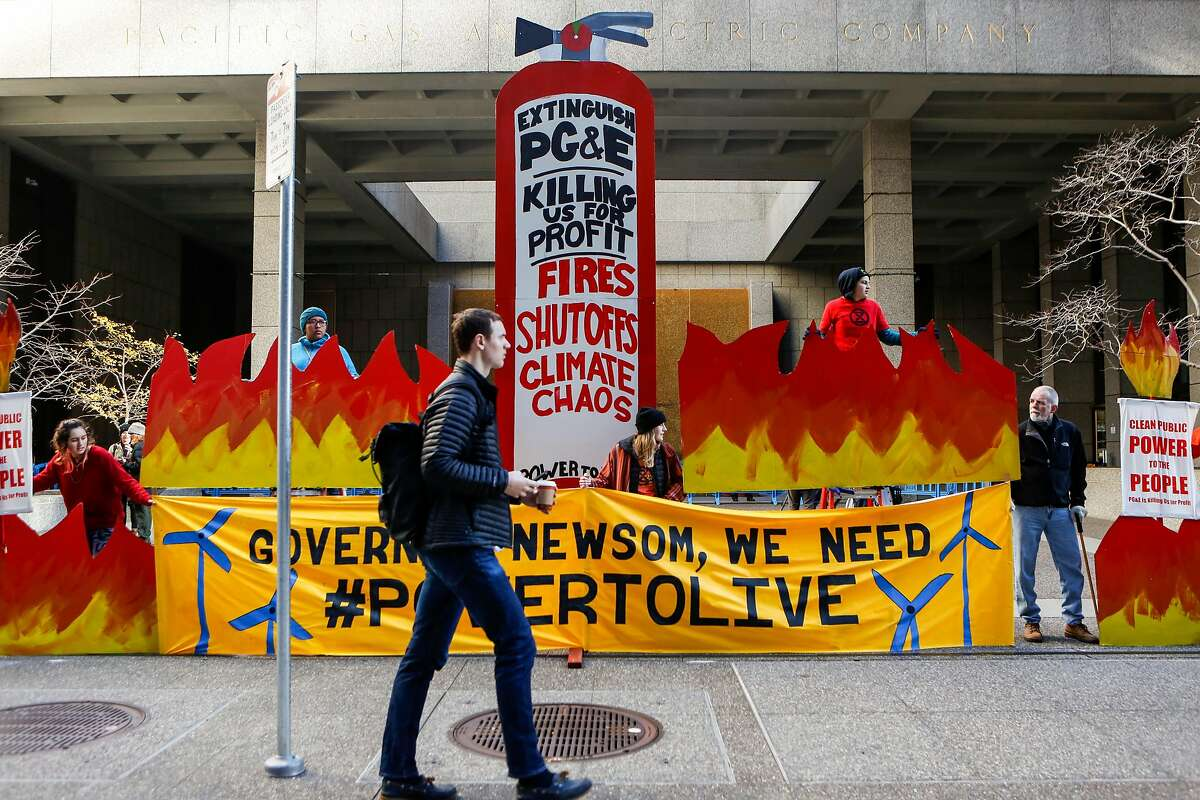 Pedestrians walk by as protesters from the Sunshine Movement block the entrance to PG&E headquarters as other chained themselves to entrance doors on Monday, December 16, 2019 in San Francisco, Calif.