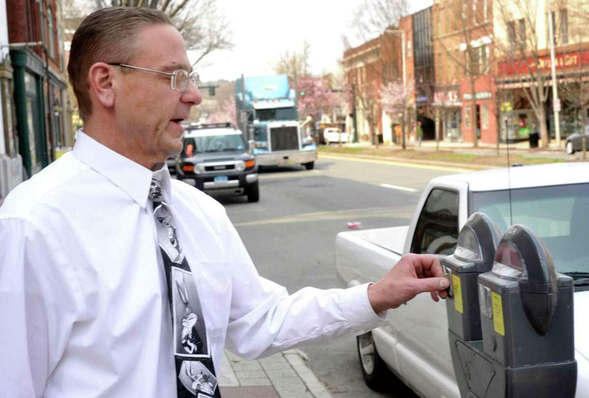 Kris Grainger, of Millbrook, N.Y., puts a coin in a parking meter on Danbury's Main Street, Monday, April 18, 2011.