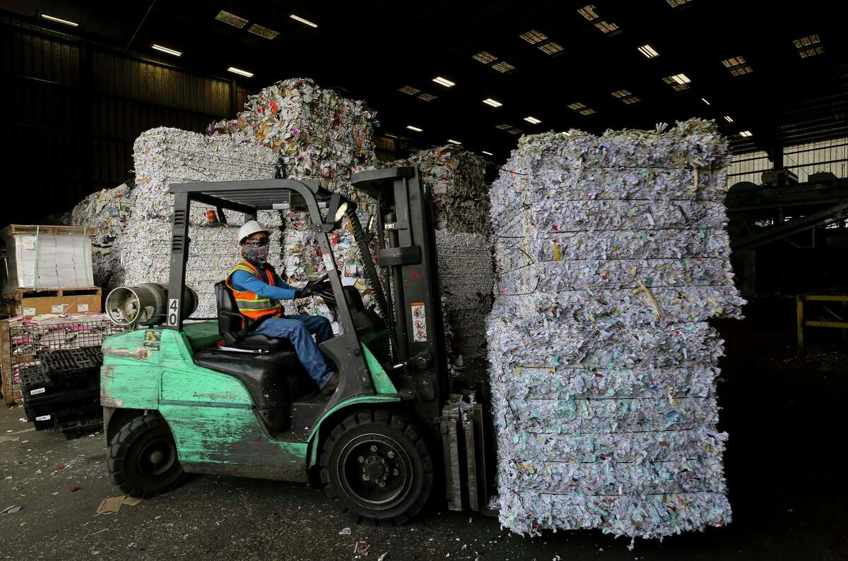 A Balcones Resources recycling center worker moves bundles of shredded paper inside the facility Monday, Dec. 9, 2019, in Austin, Texas.