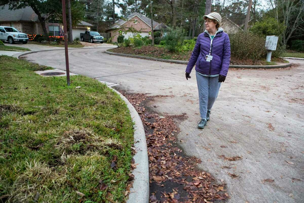 Nora Dool goes on her morning walk past a yard damaged by feral hogs on Wednesday, Dec. 11, 2019, in The Woodlands. Feral hogs have been a problem in the neighborhood, damaging yards. Residents are also wary of the danger the hogs pose to their safety.