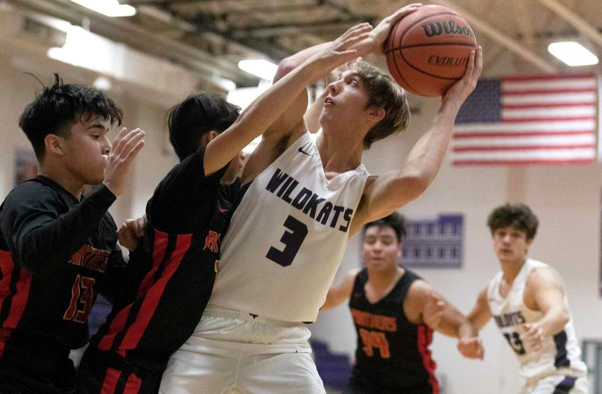 Willis guard Coleman Davis (3) is fouled by Caney Creek point guard Jerry Nguyen (1) alongside guard Arnold Deras (13) during the second quarter of a District 20-5A high school basketball game at Willis High School, Friday, Dec. 20, 2019, in Willis.