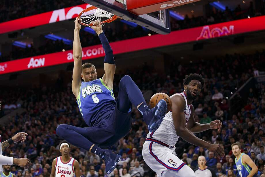 The Mavericks' Kristaps Porzingis dunks over the 76ers Joel Embiid for two of his 22 points in Dallas' win in Philadelphia, improving their road record to 11-2. Photo: Chris Szagola / Associated Press
