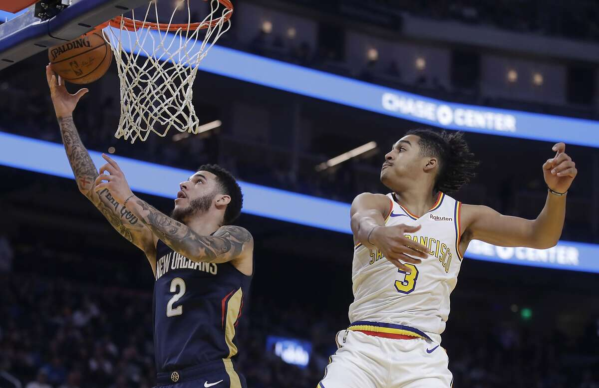New Orleans Pelicans' Lonzo Ball, left, lays up a shot past Golden State Warriors' Jordan Poole (3) during the first half of an NBA basketball game Friday, Dec. 20, 2019, in San Francisco. (AP Photo/Ben Margot)