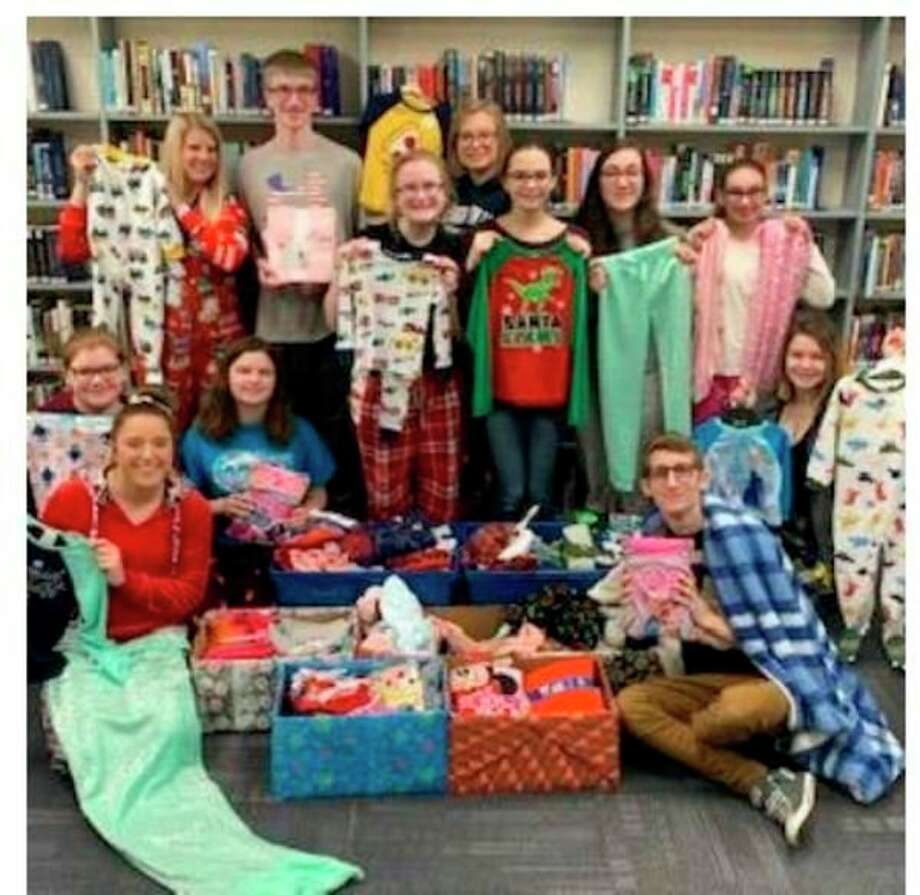 Hemlock students pose with pairs of pajamas they collected during the holiday season. (Photo provided)