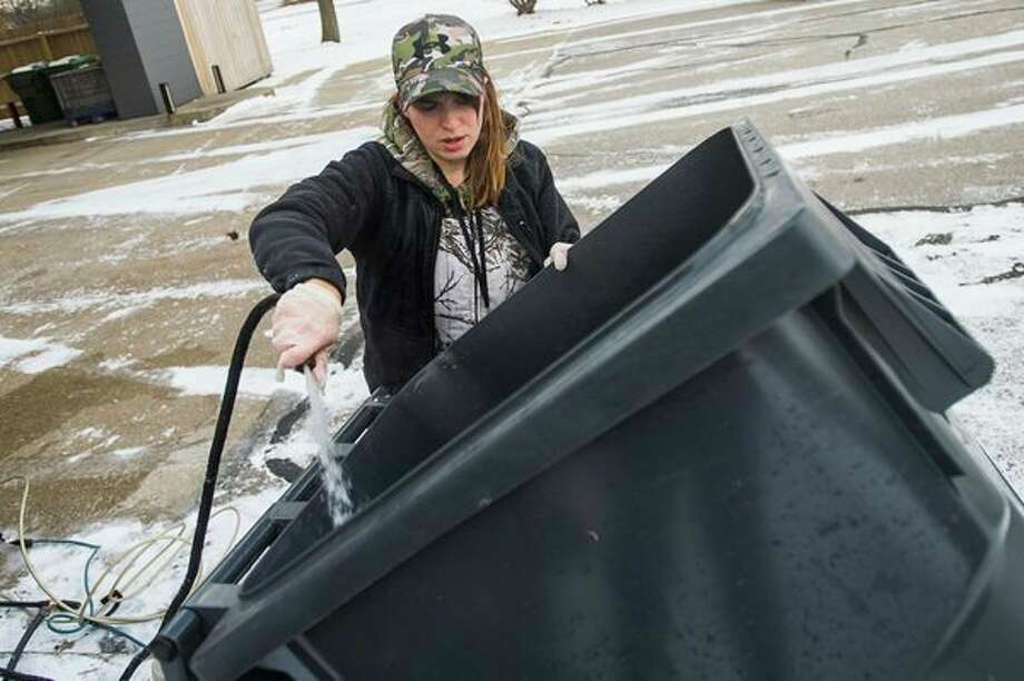 Midland resident Audrey Mills works to clean out trash bins at Grove Tea Lounge as part of her new business, Better Bins, Wednesday in Midland. (Katy Kildee/kkildee@mdn.net)