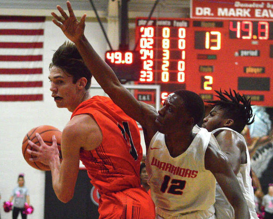 Edwardsville's Brennan Weller, left, pulls down a rebound while being guarded by two Granite City players. Photo: Scott Marion/The Intelligencer
