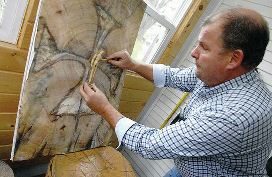 Woodcutter Tom Durand shows the position of the crucified Christ that he sees in the log at his home in Roanoke. Photo: David Proeber   The Pantagraph (AP)