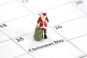 Miniature Santa Claus standing on a calendar with Christmas Day printed on it.