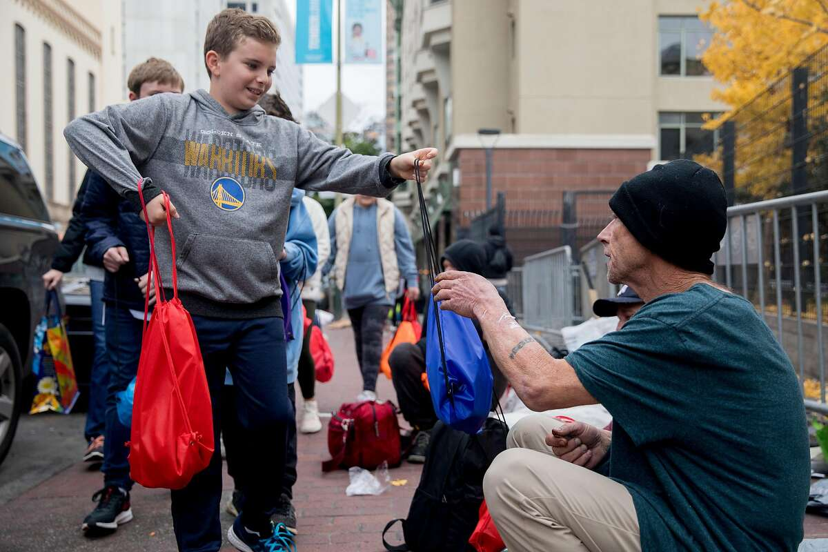 Chase Kendall, 11, of San Mateo hands a care packages to a homeless man in the Tenderloin neighborhood of San Francisco, Calif. Saturday, December 21, 2019.