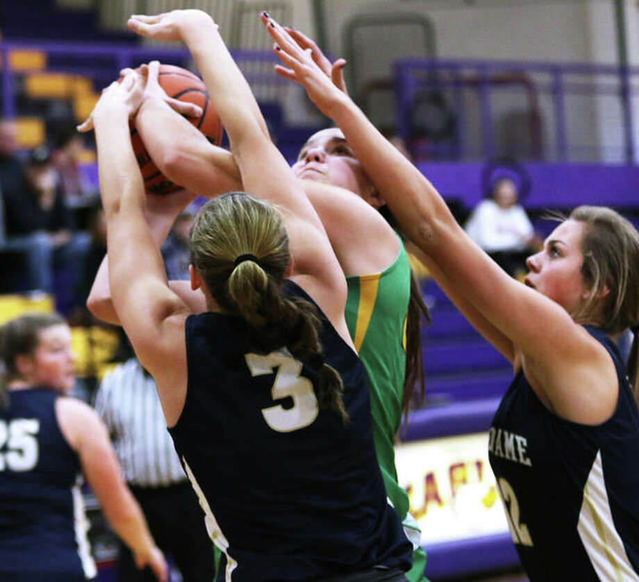 Southwestern's Korrie Hopkins draws a foul on her shot contested by Quincy Notre Dame's Abbey Schreacke and Sydney Hummert (right) on Saturday afternoon at the CM/Adidas Shootout in Bethalto. Photo: Greg Shashack / The Telegraph
