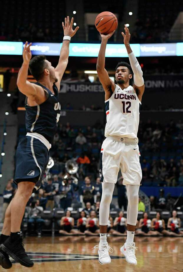 UConn's Tyler Polley (12) shoots as New Hampshire's Mark Carbone (5) defends during a game last season in Hartford. Photo: Jessica Hill / Associated Press / Copyright 2018 The Associated Press. All rights reserved