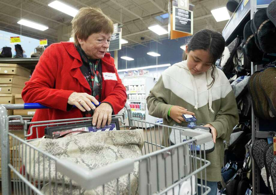 Mona Heffernan, left, helps Gygy Arroyo look for a gift for her mother during the annual Panorama Samaritans shopping event at Kroger Saturday in Willis. The annual event allowed 100 children from the area to choose Christmas presents to themselves and their family. Photo: Jason Fochtman, Houston Chronicle / Staff Photographer / Houston Chronicle