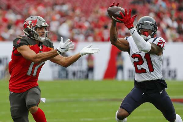 Houston Texans cornerback Bradley Roby (21) leaps in front of Tampa Bay Buccaneers wide receiver Justin Watson (17) for an interception that he returned for a touchdown during the first quarter of an NFL football game at Raymond James Stadium on Saturday, Dec. 21, 2019, in Tampa.