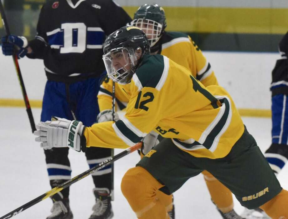 Hamden's Jack Shane (12) celebrates a first-period goal against Darien in Hamden on Saturday. Photo: David Stewart / Hearst Connecticut Media