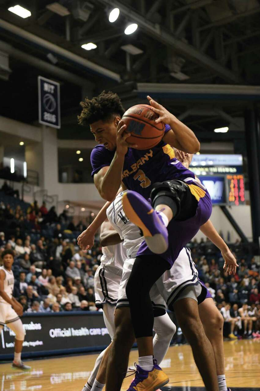 Point guard Jojo Anderson, making his first career start for UAlbany, grabs a rebound Saturday against Monmouth in West Long Branch, N.J. (Photo courtesy Monmouth athletics)