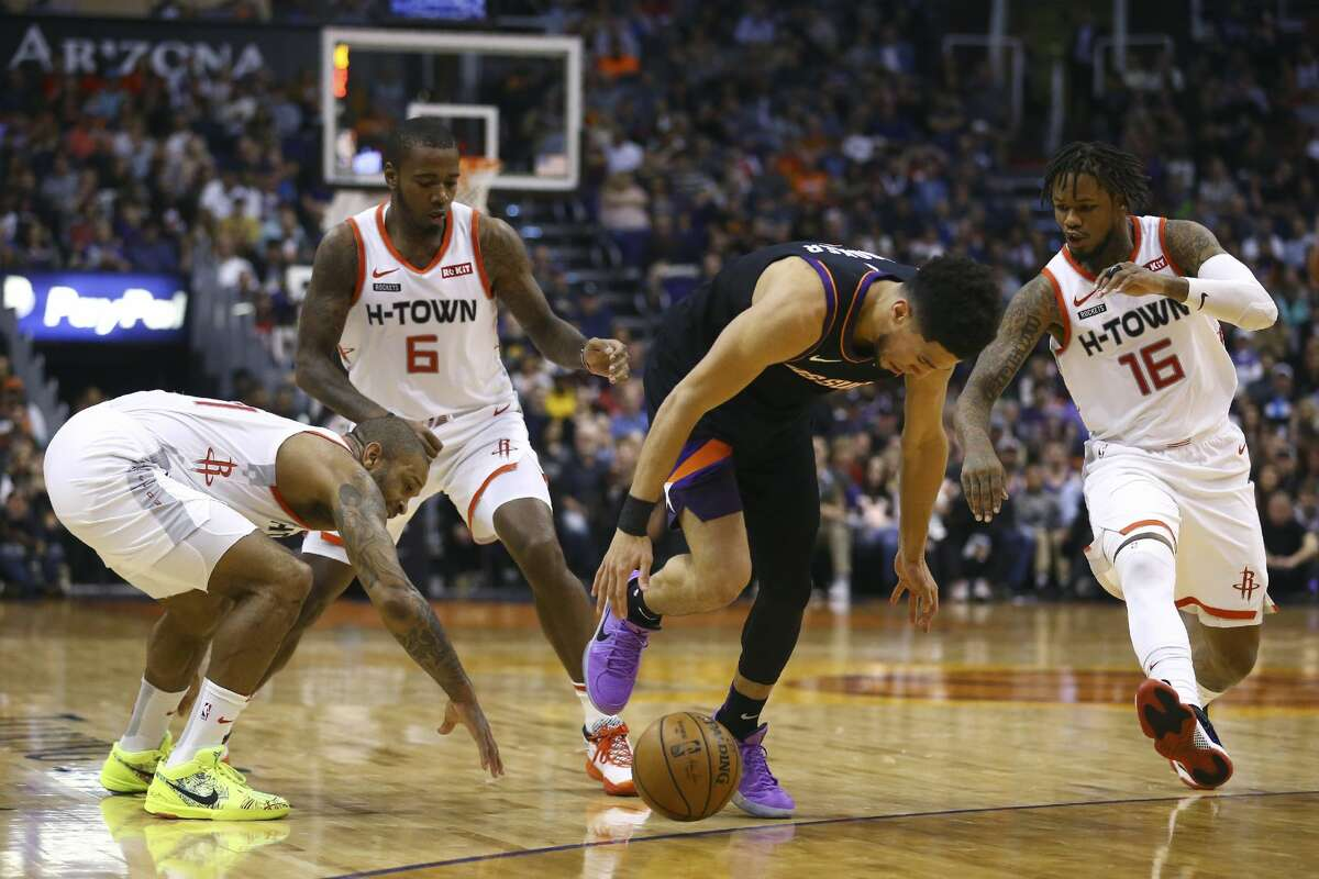 Phoenix Suns guard Devin Booker, second from right, loses the ball as Houston Rockets forward PJ Tucker, left, Rockets forward Gary Clark (6) and Rockets guard Ben McLemore (16) defend during the second half of an NBA basketball game, Saturday, Dec. 21, 2019, in Phoenix. The Rockets defeated the Suns 139-125. (AP Photo/Ross D. Franklin)