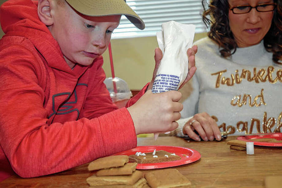 Gage Rice, 6, of Bluffs puts icing on the roof of his gingerbread house Saturday with the help of his mother, Julie, at the Jacksonville Public Library. Photo: Samantha McDaniel-Ogletree | Journal-Courier