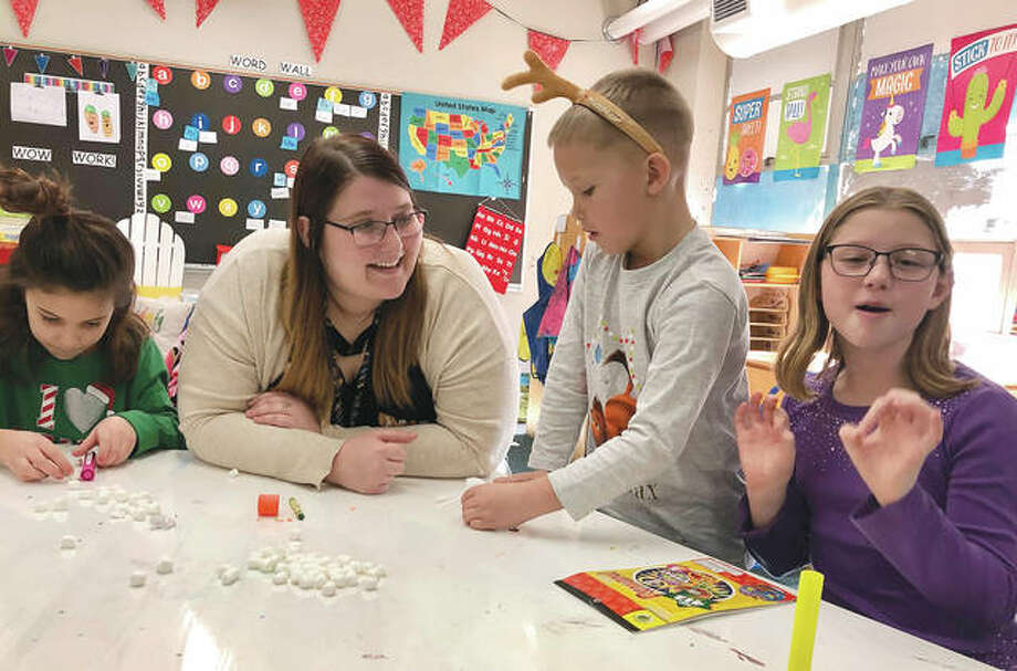 Erin Huff, a kindergarten teacher at Waverly Elementary School, works with Ava Turner (from left), Benton Ryan and Haven Green on estimating measurements using mini-marshmallows in Waverly. Huff, a 24-year-old teacher in her third year, says relatively low pay, stress and workload often discourage young people from pursuing teaching degrees, leading to a current shortage of classroom teachers in Illinois. A nonprofit teacher-training program is using a $750,000 addition to the state budget to speed up certification to address a rampant teacher shortage. Photo: John O'Connor | AP