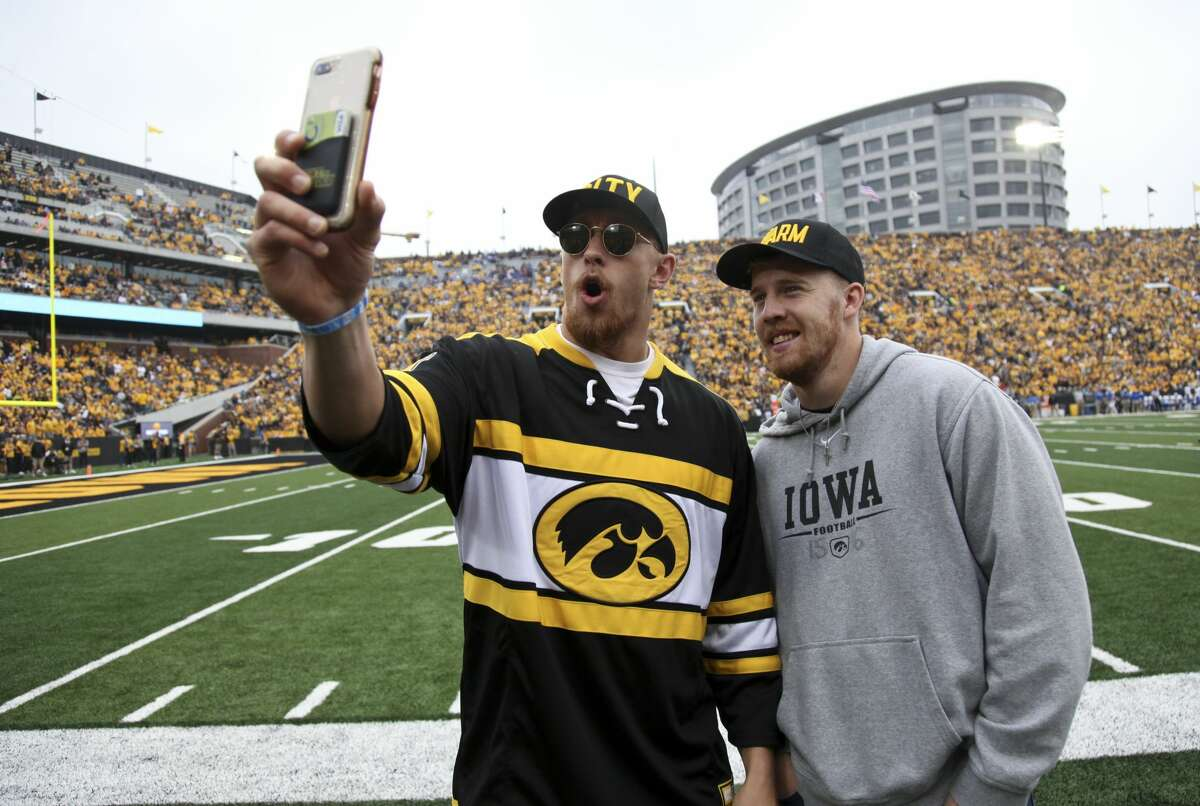 Tight end George Kittle and quarterback C.J. Beathard of the San Francisco 49ers take photos on the field during the match-up between their alma mater Iowa Hawkeyes and the Middle Tennessee Blue Raiders on September 28, 2019 at Kinnick Stadium in Iowa City.