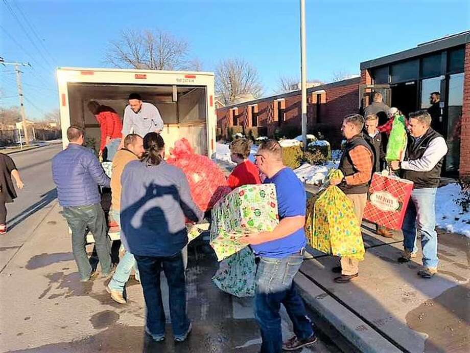 Volunteers at Icon Mechanical in Granite City help load a truck with gifts for the Mid-Town Moms' Christmas Giveaway on Dec. 20. This year the group collected about 3,000 toys for area children.