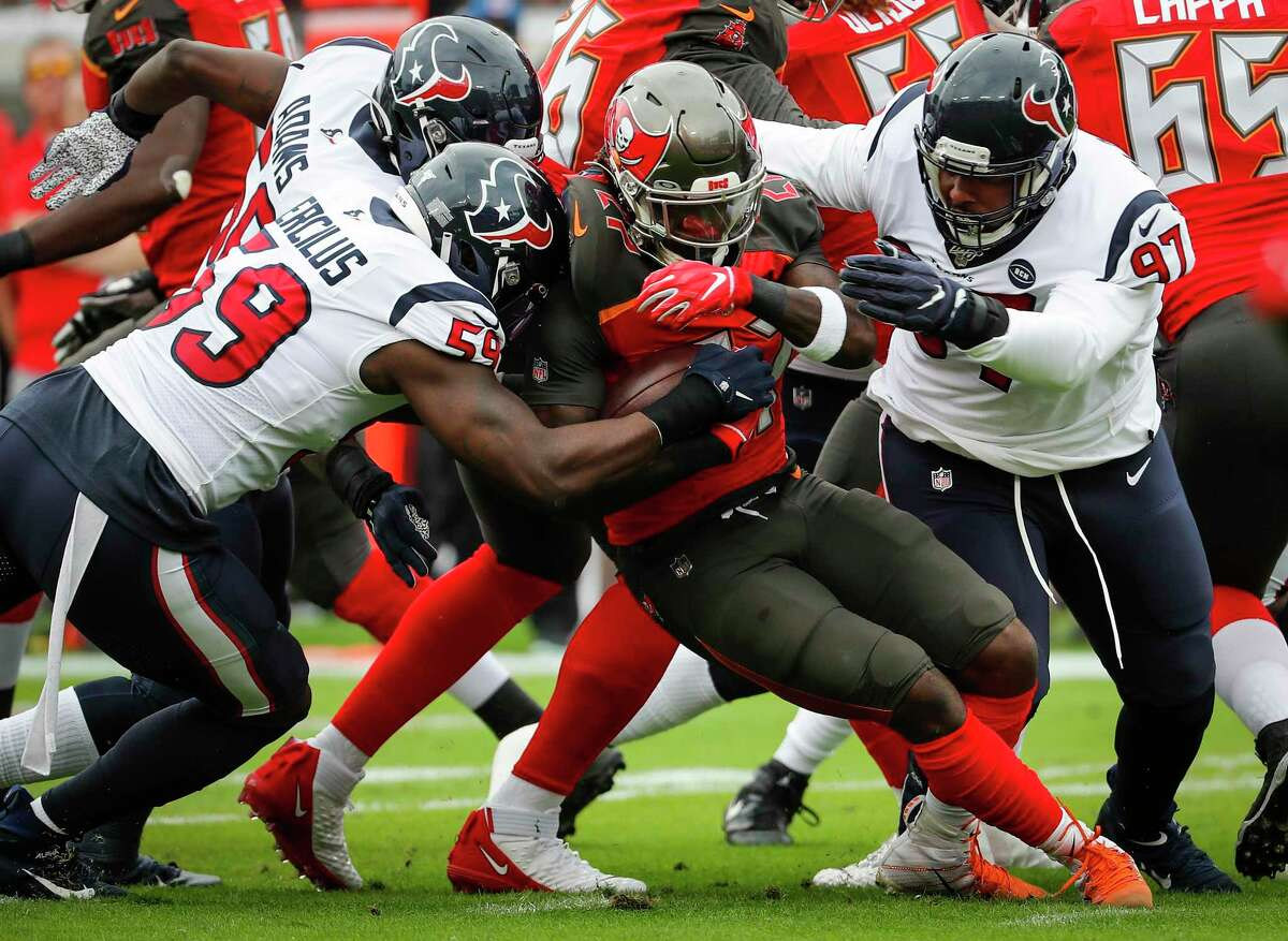 Houston Texans defensive end Angelo Blackson (97) and outside linebacker Whitney Mercilus (59) stop Tampa Bay Buccaneers running back Ronald Jones (27) for a loss during the first quarter of an NFL football game at Raymond James Stadium on Saturday, Dec. 21, 2019, in Tampa.