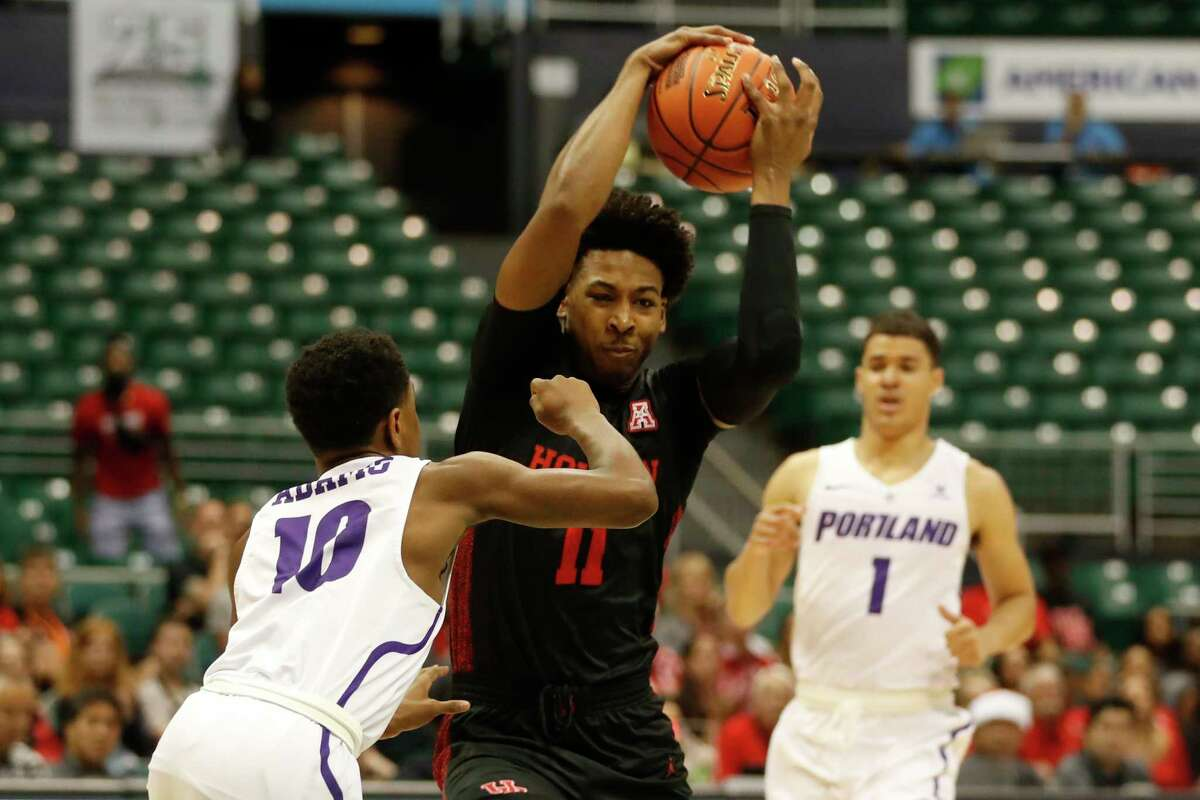 Houston guard Nate Hinton (11) tries to get around Portland guard Chase Adams (10) during the first half of the NCAA college basketball game Sunday, Dec. 22, 2019, in Honolulu. (AP Photo/Marco Garcia)