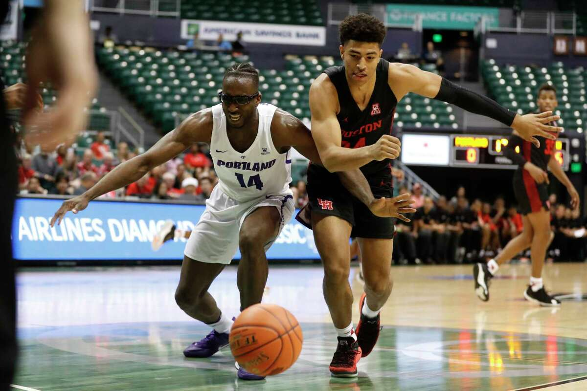 Portland forward Tahirou Diabate (14) and Houston guard Quentin Grimes (24) chase the ball during the first half of an NCAA college basketball game Sunday, Dec. 22, 2019, in Honolulu. (AP Photo/Marco Garcia)