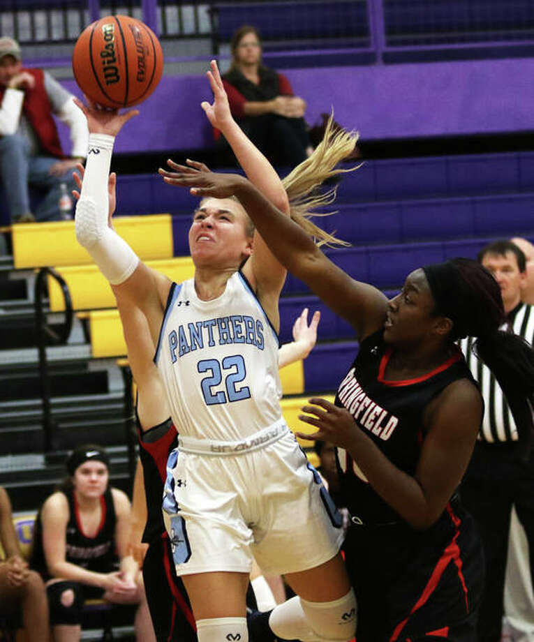 Jersey's Clare Breden (22) splits defenders to put up a shot contested by Springfield's Virtuous Komolafe on Saturday night at the CM/Adidas Shootout in Bethalto. Photo: Greg Shashack / The Telegraph